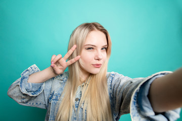 Attractive blond woman taking selfie showing Peace sign with fingers on isolated blue background