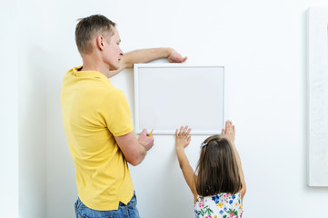 Father and daughter are hanging the picture.