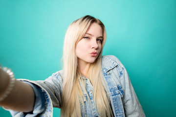 Positive blond-haired woman taking selfie doing duck face lisolated on blue background
