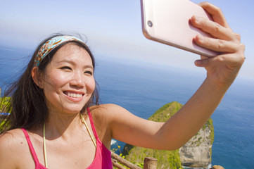 young beautiful and happy Asian Korean tourist woman smiling taking selfie portrait with mobile phone in beach sea cliff landscape background