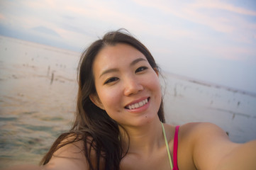 young happy and beautiful Asian Korean tourist woman taking self portrait selfie with mobile phone smiling having fun at sunset beach