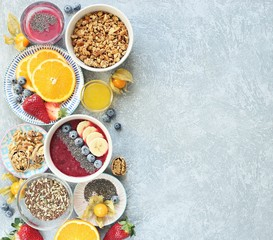Breakfast food table. Healthy breakfast or brunch set, meal variety with granola, smoothie ,fresh berries, fruits and various of topping. Overhead view, copy space