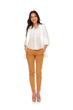 sexy businesswoman standing with hands in pockets while smiling