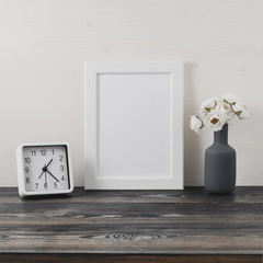 White frame, flower in vaze, clock on dark gray wooden table against the white wall with copy space. Mock up.