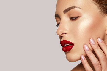Gorgeous Young Brunette Woman face portrait. Beauty Model Girl with bright eyebrows, perfect make-up, red lips, touching her face. Sexy lady makeup. Space for text. Banner