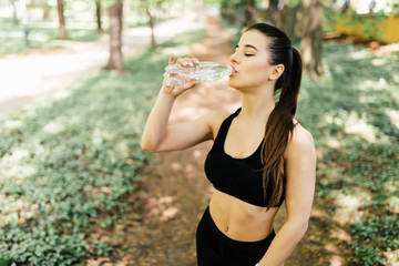Beautiful sport athletic woman running in a park and drinking water