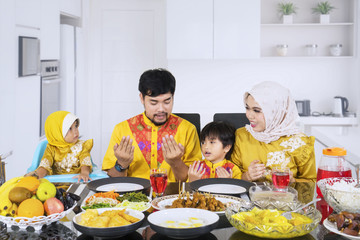 Young family praying before breaking fast