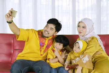 Muslim family taking selfie photo at home