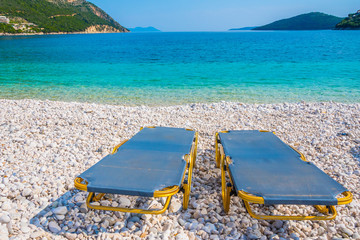 A pair of sunbeds by the sea at Poros beach in Lefkada ionian island in Greece