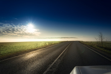 Summer Landscape with Field and Country Road Leading in the Fog. Dramatic Sky at Sunset Background. Beautiful Nature Background.