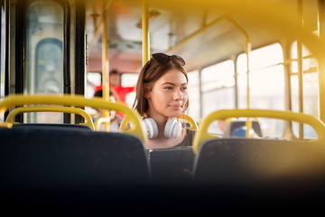 A young pretty woman with headset hanging on her neck is using tablet while sitting on a bus seat.
