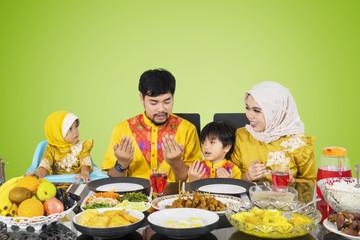 Asian family praying before their break fast