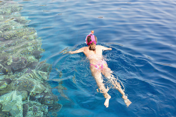 Snorkeling gear.  Snorkeling girl in full face mask.  Underwater swimming in Red sea near a coral reef. Tropical vacation activity snorkeling