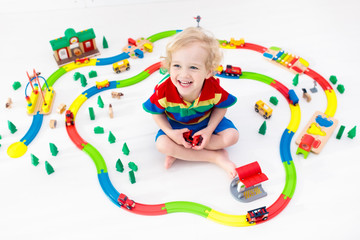 Wall Mural - Child with toy train. Kids wooden railway.