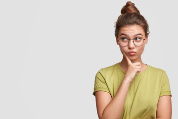 Horizontal shot of beautiful female model with hair knot, wears big spectacles and casual t shirt, keeps figer under chin as thinks about something, poses against white backgroud with copy space