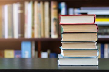 A stack of books on the background of bookshelves.