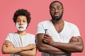 Portrait of stunned African American male with crossed hands, holds razor in hands and his son with shaving gel, looks surprisingly at camera, isolated over pink background. Skin care concept
