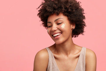 Sideways shot of cheerful slim lady with Afro hairstyle, has spangles on cheeks, smiles broadly, demonstrates white perfect teeth, dressed in casual t shirt, looks happily down, poses over pink wall