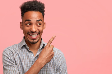 African American male with cheerful expression, indicates at blank copy space, advertises or shows something pleasant, looks joyfully upwards, isolated over pink background. Dark skinned hipster guy