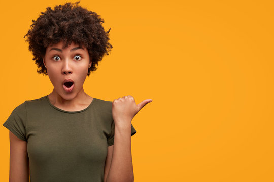 Photo of greatly surprised dark skinned female with bushy Afro haircut, wears casual t shirt, indicates at yellow blank copy space, keeps mouth widely opened, being astonished with something.