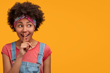 Lovely secret African American female makes silence gesture, has happy expression, looks mysteriously aside at yellow blank space, being in high spirit. People, ethnicity, conspiracy concept
