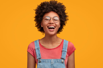 Glad African American female with positive expression, laughs joyfully as watches funny movie with friend, spends leisure time in good company, has specific appearance, wears round spectacles