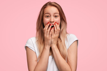 Astonished beautiful female with long hair, covers mouth with happiness, recieves proposal from boyfriend, has unexpected event in life, isolated over pink background. People and emotions concept