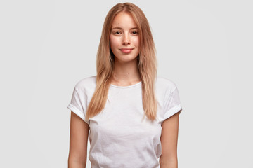 Portrait of pleased beautiful European female with long hair, dressed in casual t shirt, isolated on white background. Attractive woman student meets with groupmates. Facial expressions concept
