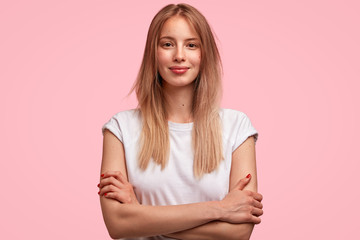 Wall Mural - Isolated shot of good looking female student dressed casually, spends weekend at home, listens attentively mother`s instructions, going to have walk with boyfriend or friends, has attractive look