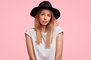 Adorable female youngster or student wears trendy black hat and casual white t shirt, looks seriously at camera, has no make up, healthy skin and light straight hair, isolated on pink background