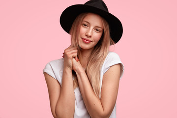 Pretty delighted female with appealing appearance looks happily at camera, keeps hands together, being pleased to recieve commpliment, poses in studio. Beautiful young woman in stylish black hat