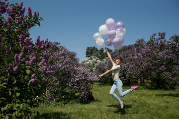 A woman jumps with balloons while she poses for a picture at a park in Kiev