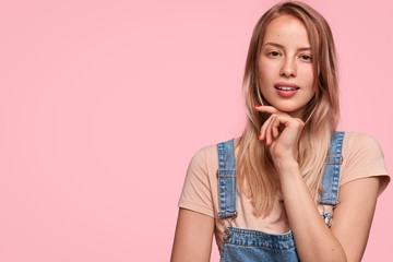 Pretty lovely young female hipster looks mysteriously and confidently, holds chin, wears t shirt and jean overalls, poses against pink background with blank copy space for your promotional text