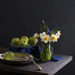 Still life with daffodils and apples