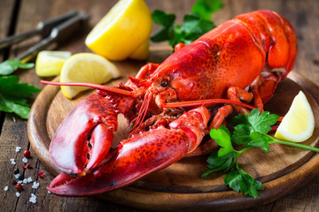 Acrylic Prints Seafoods Steamed red lobster on a wooden cutting board with parsley and lemon