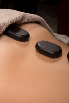 Close up of stones at back of woman in spa salon