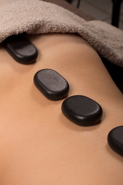 close up of Woman lying with spa stones at her back