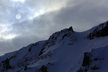 Round Sun in Cloudy Sky, over a Snowy Ridge. Svalbard, Norway