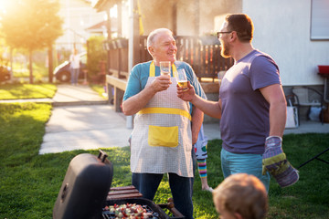 Elderly Father and mature son are saluting with the beer in front of the grill in their house backyard on a beautiful day.