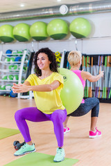 Two young women doing squat exercises standing back to with a Swiss ball between them. Female athletes working-out in gym.