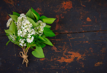 bouquet of white lilac flowers with green leaves on a black wooden retro grunge background with copy space