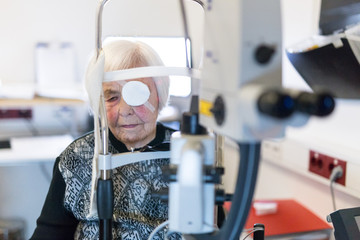 Elderly 95 years old woman wearing eye pathc after laser surgery procedure at ophthalmology clinic. Age, vision, surgery, eyesight and people concept.