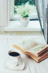 a Cup of black coffee and an open book on a white wooden vintage retro table and a bouquet of Lily of the valley flowers on the windowsill at the rustic house in the spring morning
