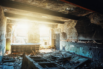 Ruins of old abandoned building, damaged in war, inside destroyed room with sunlight, disaster and devastation concept, broken walls and furniture