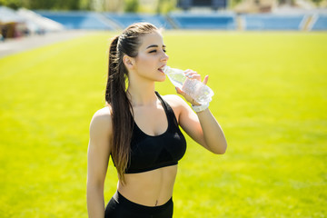 Sport, healthy lifestyle. Young sport girl drinking water on stadium.