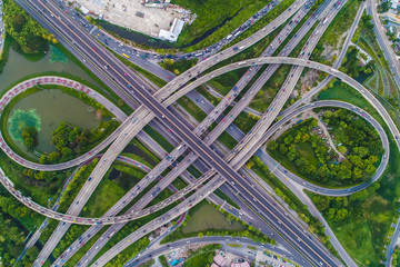 Aerial view car movement on traffic junction road with green tree park