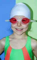 girl in a swimsuit, cap and swimming goggles