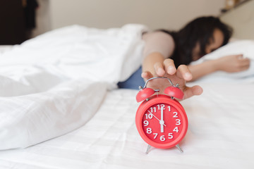 Soon to wake up for sleeping attractive asian young woman with alarm clock.