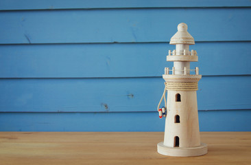 vacation and summer image with lighthouse over blue wooden planks background.