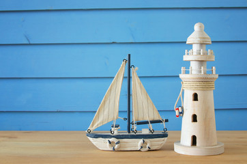 vacation and summer image with lighthouse and boat over blue wooden planks background.